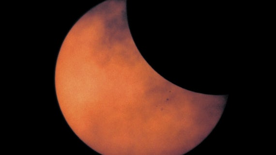 Sky with bright orange sun partly covered by moon