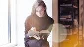 Young woman reading in library