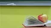 Apple on book in a calssroom