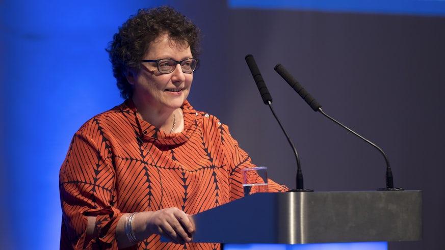 Elin Jones AM wears an orange top and speaks at a podium.