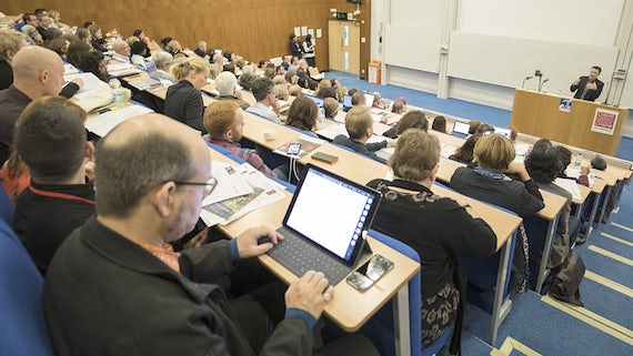 A full lecture theatre watch a speaker from 2017's conference