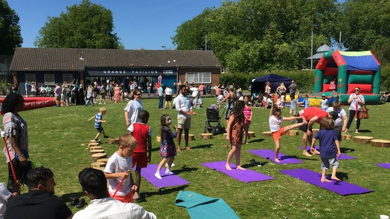 Families on the grass outside the Grange Pavilion on a sunny day with bouncy castle and purple yoga mats