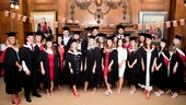 Group image of male and female students in their graduation gowns
