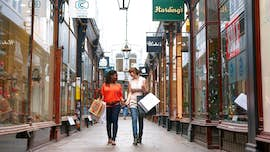 Two women walking through Cardiff arcade
