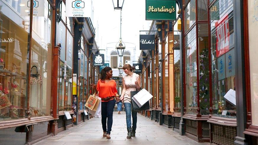 Two women walking through Cardiff arcade