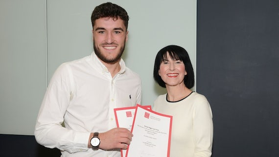 Male student collects two awards from Dean