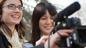 Two female student journalists using film equipment
