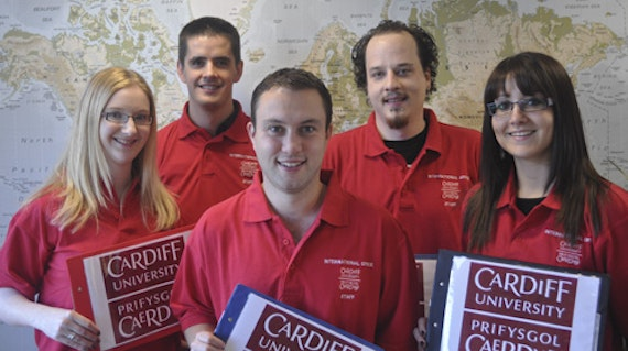 Three men and two women standing in front of a map. They are all wearing red polo shirt with white Cardiff University logos printed on them.