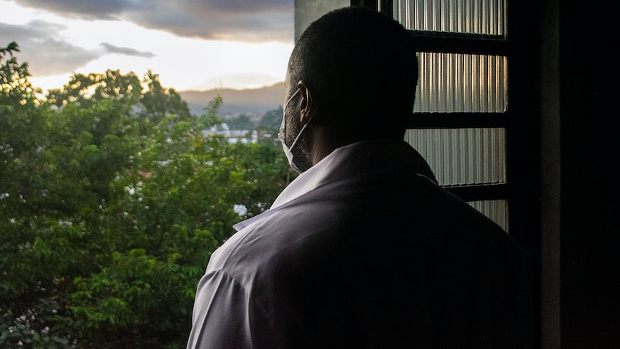 Stock image of man in a mask looking out of the window