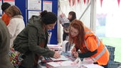A unistaff helper gives information to visitor