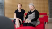 Katie Featherstone and Jackie Askey sitting on red sofa