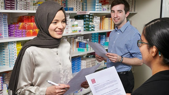 Three students learn how to dispense medicines at the School of Pharmacy