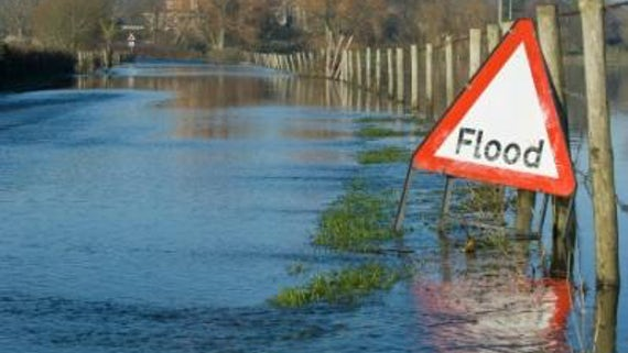 Flooded road with Flood triangle warning sign