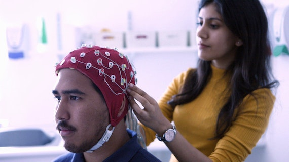Woman attaching an EEG cap and electrodes to a male study participant's head