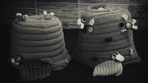 Two knitted beehives on a table