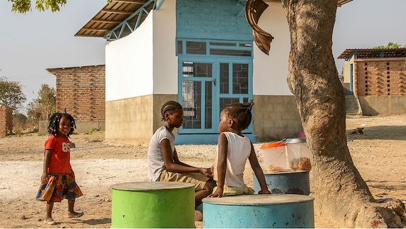 Three children play under a tree, in front of a building on the site of Shiyala School.