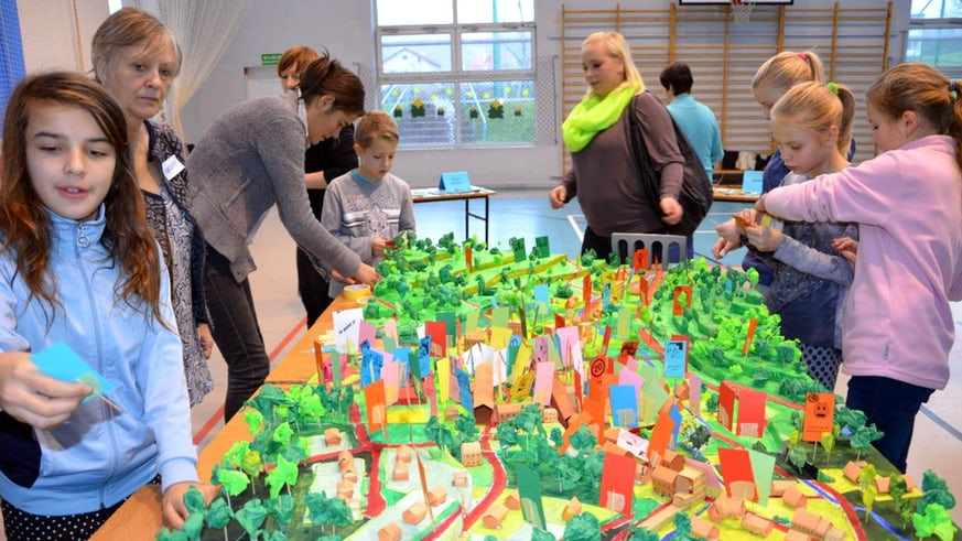 Children and women clustered around a model of a neighbourhood