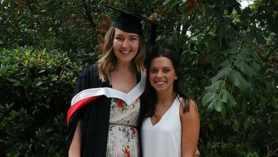 Image of Annabel Reville in a graduation gown, pictured with Crime and Security Research Assistant Bethan Davies.