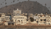 The town of Pushkar in India with historic white buildings and birds in mid-flight.