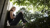 Female student sitting on a wall reading a book