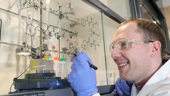 Male researcher drawing chemical equations on fume hood