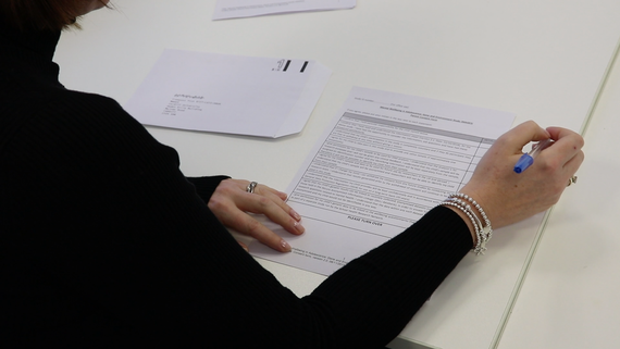 Photograph of somebody filling in a consent form