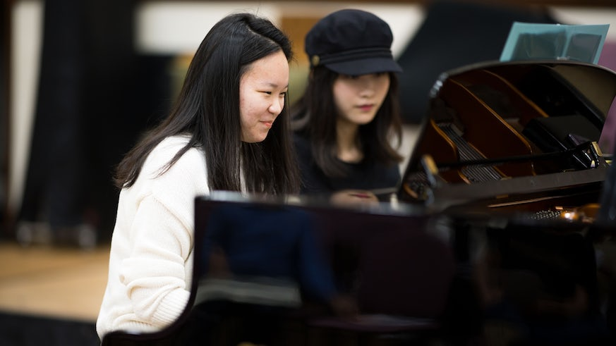 Two international students at piano