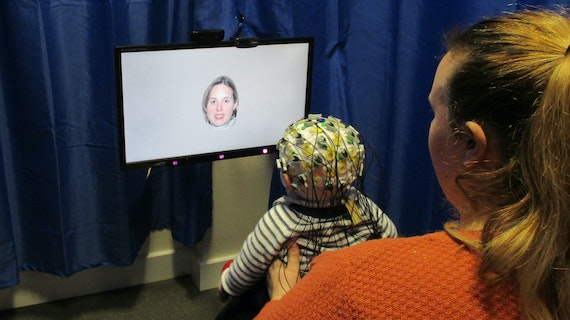 An small baby has electrodes attached to its head and views images on a computer while its mother holds it in her arms