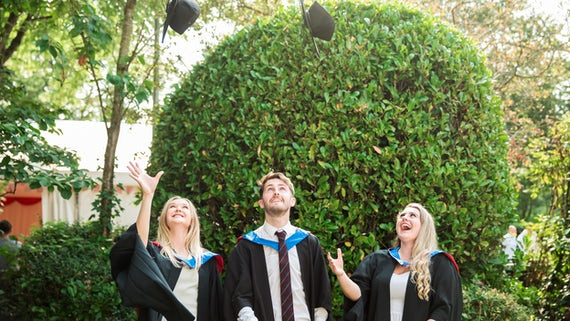 Two female and one male student wearing graduation gowns and throwing their mortar boards in the air