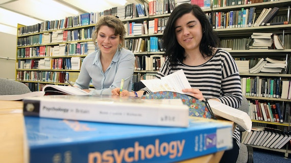 Two female students sitting at a table in a library.