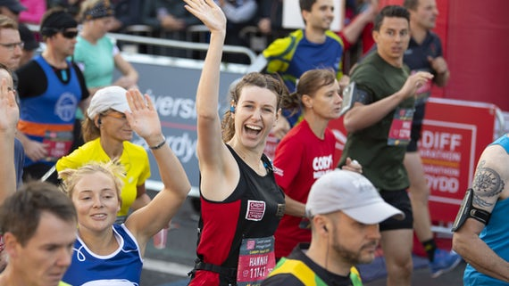 A runner smiles at the camera during Cardiff Half Marathon
