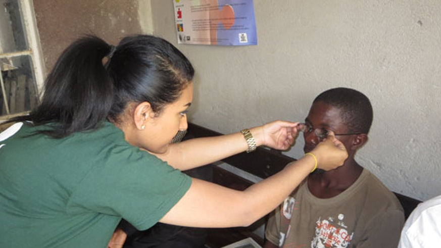 Janaka Sasitharan dispensing glasses to a patient in Zambia