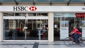 Cyclist riding past an HSBC branch.