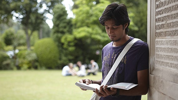 Male student reading outside Main Building