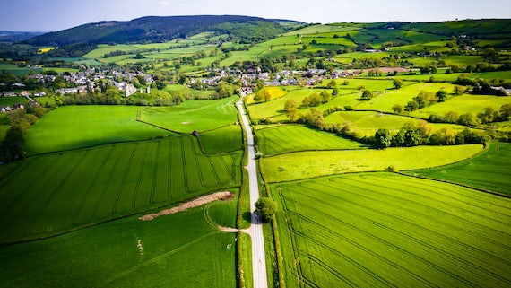 Aerial view looking down on a rural road in the UK countryside with a car racing along it. - stock photo. On a bright sunny day, farmland and crops can be seen either side of the road