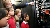 School children looking at equipment in the server room, cables coming from the back