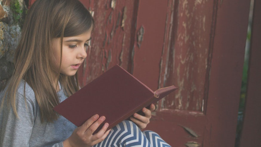 Young girl reading an old book