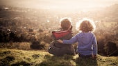 Two young children overlooking community from hillside