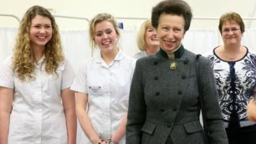 Princess Anne smiling with nursing staff standing and smiling behind