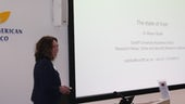 Image of female academic presenting slides at conference