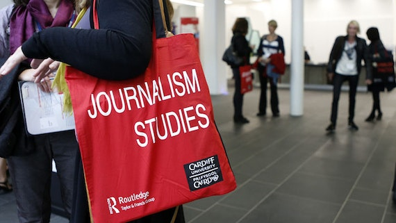 A woman holds a red bag with journalism studies written on it.