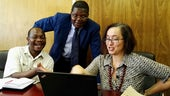 Dr Nelson Mlambo sitting with Professor Loredana Polezzi, looking at a laptop, with Professor Jairos Kangira standing behind