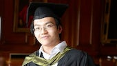 Asian male graduate smiling