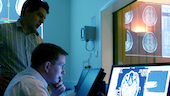 two researchers analyse a brain scan in the MR control room