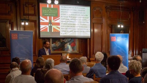 Professor Roger Awan-Scully stands speaks in front of a busy room at a launch event.
