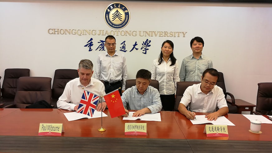 Group of male and female academics sat behind a table with British and Chinese flags in front of them