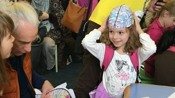 A little girl wears a makeshift brain on her head as part of brain games