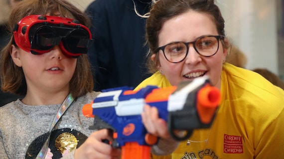 A young girl with goggles on is helped to use a nurf gun by a Cardiff University volunteer.