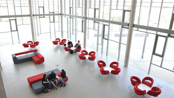 Three PG students sitting on red sofa in new building