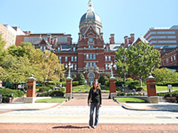 Woman standing in front of the John Hopkins University's main buidling